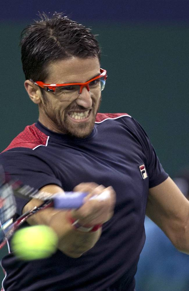 Serbia's Janko Tipsarevic returns a shot from Spain's Marcel Granollers at the Shanghai Masters Tennis tournament in the Qi Zhong Tennis Center in Shanghai, China on Monday, Oct. 7, 2013. Granollers won 6-4, 6-4