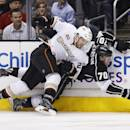 Anaheim Ducks defenseman Mark Fistric, left, checks Los Angeles Kings left wing Tanner Pearson, right, into the boards during the second period of an NHL hockey game in Los Angeles, Saturday, March 15, 2014. (AP Photo/Danny Moloshok)