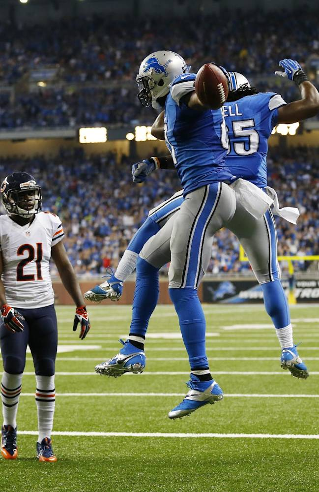 Detroit Lions wide receiver Calvin Johnson (81) and teammate running back Joique Bell (35) celebrate Johnson's touchdown as Chicago Bears strong safety Major Wright (21) look on during the second quarter of an NFL football game at Ford Field in Detroit, Sunday, Sept. 29, 2013