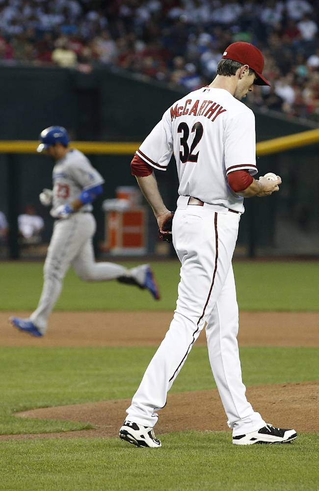 Arizona Diamondbacks' Brandon McCarthy (32) looks at a new baseball as Los Angeles Dodgers' Adrian Gonzalez (23) rounds the bases after he hit a 2-run home run during the first inning of a baseball game on Friday, April 11, 2014, in Phoenix