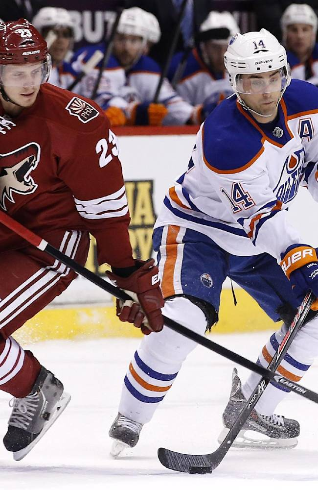 Phoenix Coyotes' Oliver Ekman-Larsson (23), of Sweden, slaps the stick of Edmonton Oilers' Jordan Eberle (14) as Eberle tries to make a pass during the first period of an NHL hockey game, Friday, April 4, 2014, in Glendale, Ariz