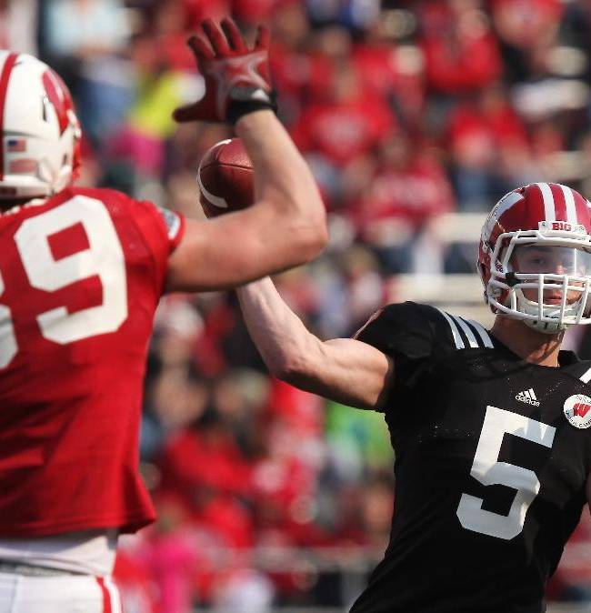 In this April 12, 2014, file photo, Wisconsin's Tanner McEvoy (5) prepares to throw a pass as Brady Kelliher (39) defends during the second half of the NCAA college football team's spring football game in Madison, Wis. The Badgers appear to have settled on dual-threat junior McEvoy as the starter, though coach Gary Andersen will not officially name one. Andersen has said both McEvoy and last year's starter, Joel Stave, will be ready no matter what