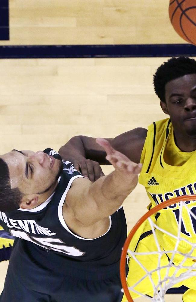 Michigan guard Derrick Walton Jr. (10) shoots over Michigan State guard Denzel Valentine (45) during the second half of an NCAA college basketball game in Ann Arbor, Mich., Sunday, Feb. 23, 2014