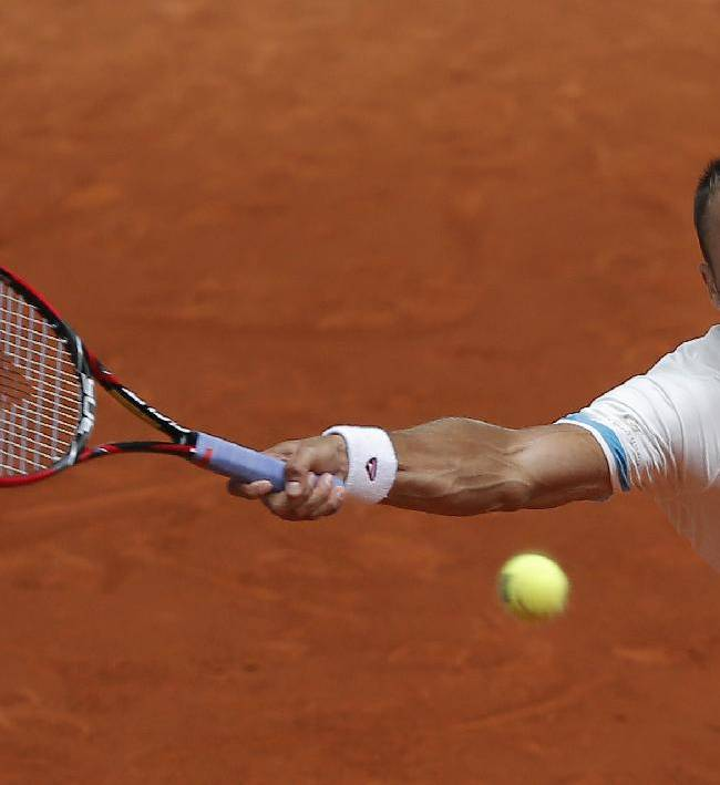 Marius Copil from Romania returns the ball during a Madrid Open tennis tournament match against Grigor Dimitrov from Bulgaria in Madrid, Spain, Wednesday, May 7, 2014
