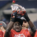 Wisconsin running back Montee Ball holds up the trophy after Wisconsin defeated Nebraska 70-31 to win the Big Ten championship NCAA college football game Saturday, Dec. 1, 2012, in Indianapolis. (AP Photo/AJ Mast)