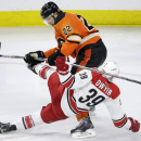 Carolina Hurricanes' Patrick Dwyer (39) goes flying after a collision with Philadelphia Flyers' Luke Schenn (22) during the third period of an NHL hockey game, Saturday, Dec. 13, 2014, in Philadelphia. Philadelphia won 5-1 The Associated Press