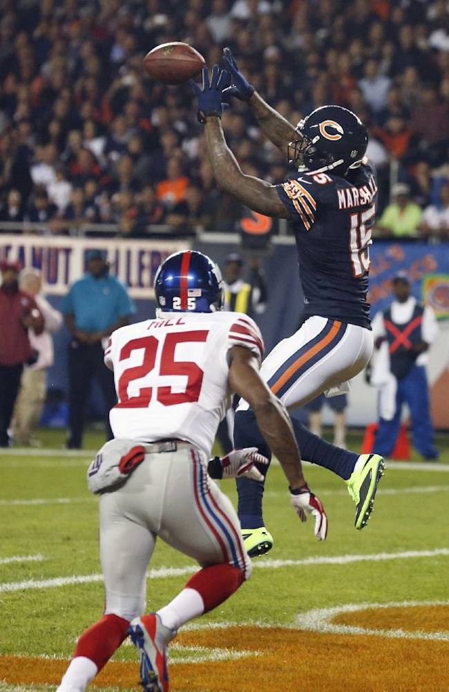 Chicago Bears wide receiver Brandon Marshall (15) makes a touchdown reception against New York Giants defensive back Will Hill (25) in the first half of an NFL football game, Thursday, Oct. 10, 2013, in Chicago