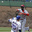 Cincinnati Reds second baseman Brandon Phillips, top, throws out Chicago Cubs' Starlin Castro at first base after forcing out Justin Ruggiano during the first inning of a baseball game in Chicago, Saturday, April 19, 2014 The Associated Press