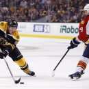 Boston Bruins' Brad Marchand (63) comes sets up his game-winning shot against Florida Panthers' Dylan Olsen (4) during overtime in an NHL hockey game in Boston, Tuesday, Nov. 4, 2014. The Bruins won 2-1 The Associated Press