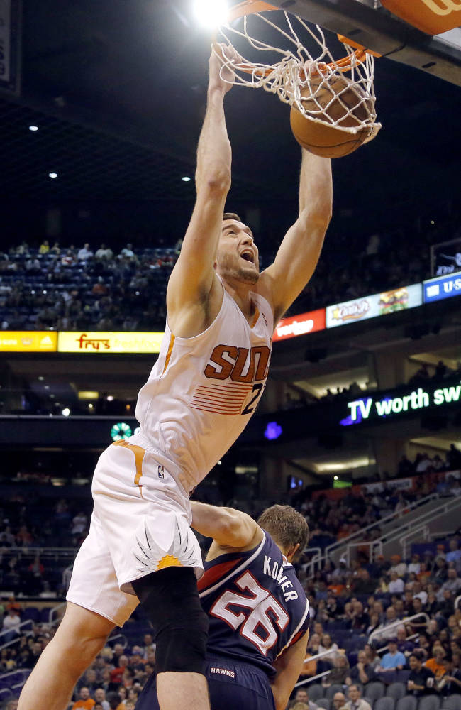 Phoenix Suns' Miles Plumlee dunks over Atlanta Hawks' Kyle Korver (26) during the second half of an NBA basketball game, Sunday, March 2, 2014, in Phoenix. The Suns won 129-120