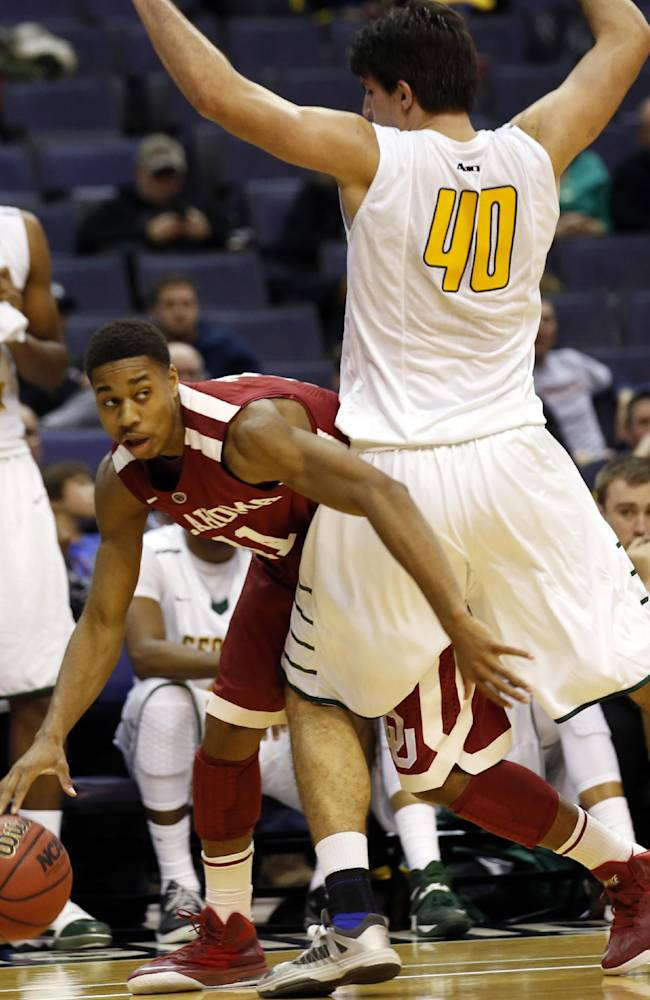 Oklahoma guard Isaiah Cousins (11) works to get around George Mason forward Marko Gujanicic (40) during the second half of an NCAA college basketball game in the BB&T Classic, Sunday, Dec. 8, 2013, in Washington. Oklahoma won 81-66