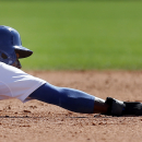 Los Angeles Dodgers' Dee Gordon holds on after sliding past second base on a steal against the Texas Rangers during a spring exhibition baseball game in Glendale, Ariz., Friday, March 7, 2014 The Associated Press