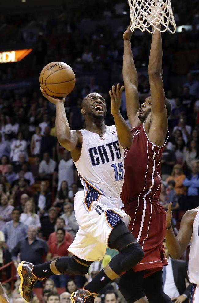 Charlotte Bobcats' Kemba Walker (15) shoots as Miami Heat's Chris Bosh defends during the second half of an NBA basketball game, Sunday, Dec. 1, 2013, in Miami. The Heat won 99-98