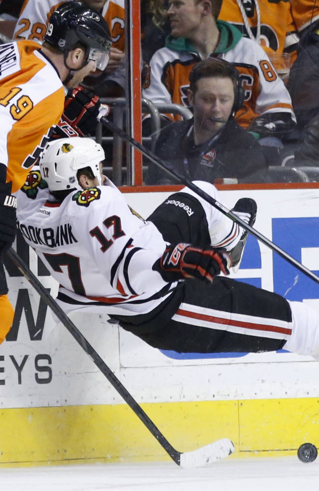 Philadelphia Flyers' Scott Hartnell, left, knocks Chicago Blackhawks' Sheldon Brookbank to the ice during the first period of an NHL hockey game, Tuesday, March 18, 2014, in Philadelphia