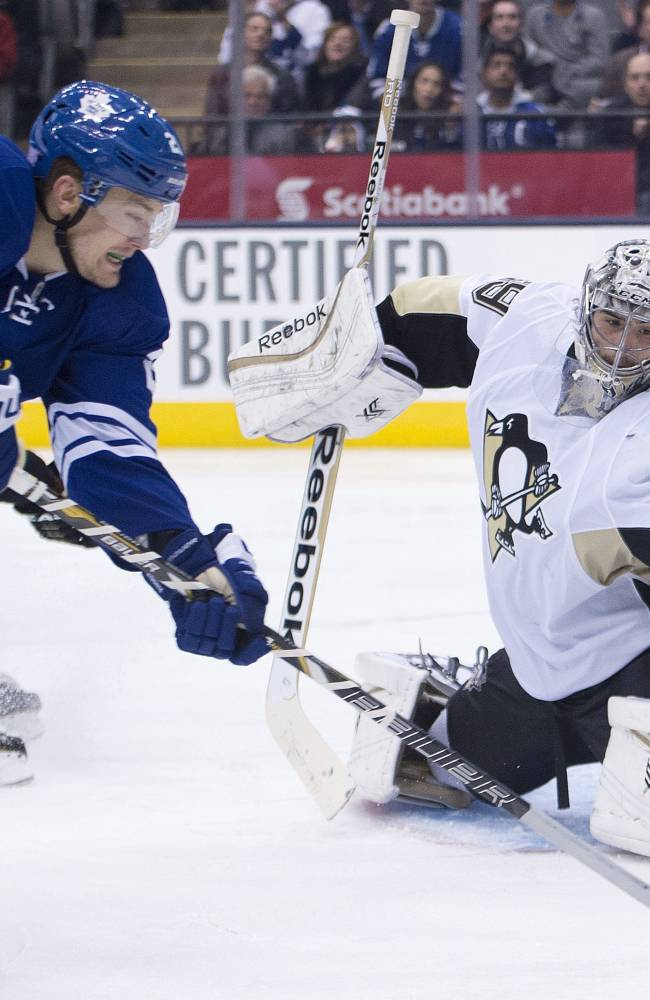 Toronto Maple Leafs forward James van Riemsdyk, left, gets stopped by Pittsburgh Penguins goalie Marc-Andre Fleury, right, during the second period of an NHL hockey game, Saturday, Oct. 26, 2013 in Toronto