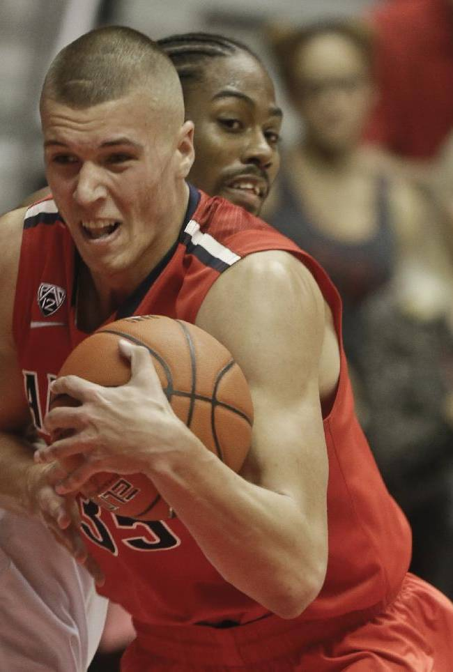 Arizona center Kaleb Tarczewski blast his way through San Diego State forward Josh Davis while going to the basket during the second half of Arizona's 69-60 victory in a NCAA college basketball game Thursday, Nov. 14, 2013, in San Diego