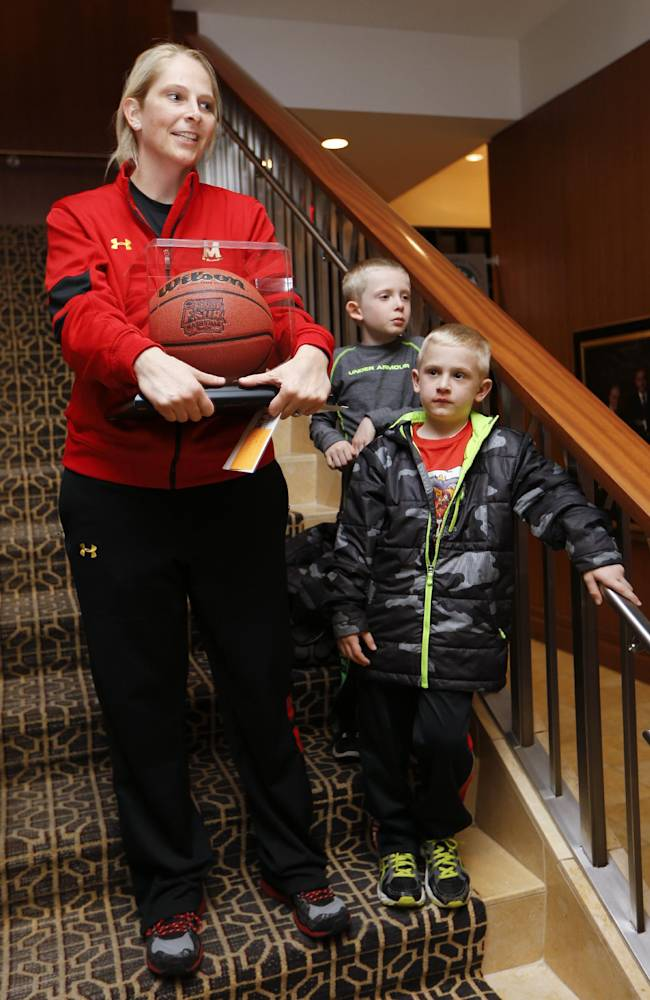 Maryland coach Brenda Frese holds a ball the team was presented after arriving at their hotel for the NCAA women's Final Four college basketball tournament, Thursday, April 3, 2014, in Nashville, Tenn. With Frese are her 6-year-old twin sons, Tyler, right, and Markus Thomas. Maryland is scheduled to play Notre Dame in a semifinal on Sunday