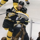 Boston Bruins center Patrice Bergeron (37) is embraced by teammate Zdeno Chara (33) after scoring the game winning goal off T