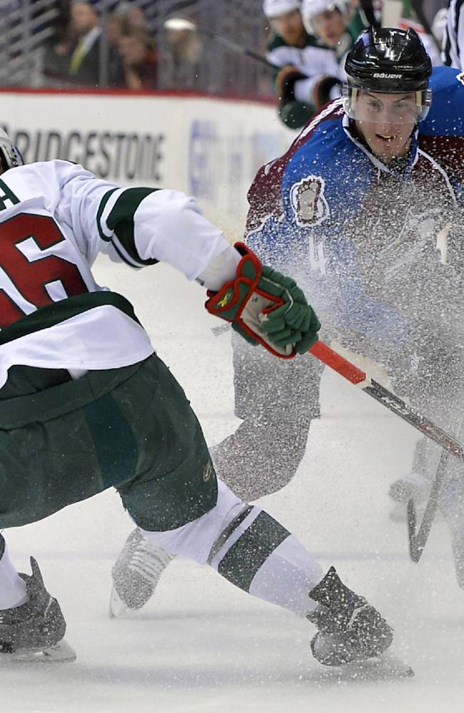 Colorado Avalanche defenseman Tyson Barrie (4) and Minnesota Wild left wing Erik Haula (56), from Finland, skate in a spray of ice during the second period in Game 1 of an NHL hockey first-round playoff series on Thursday, April 17, 2014, in Denver