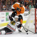 Chicago Blackhawks' Marcus Kruger, left, of Sweden, tries to hang onto the puck as Philadelphia Flyers' Nicklas Grossmann, center, of Sweden, and Steve Mason defend during the first period of an NHL hockey game, Wednesday, March 25, 2015, in Philadelphia. (AP Photo/Matt Slocum)