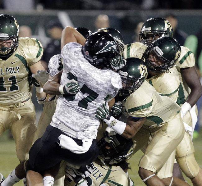 Portland State tight end Cameron Thompson (37) is tackled by a score of Cal Poly defenders during the first half of an NCAA college football game in Portland, Ore., Thursday, Sept. 26, 2013
