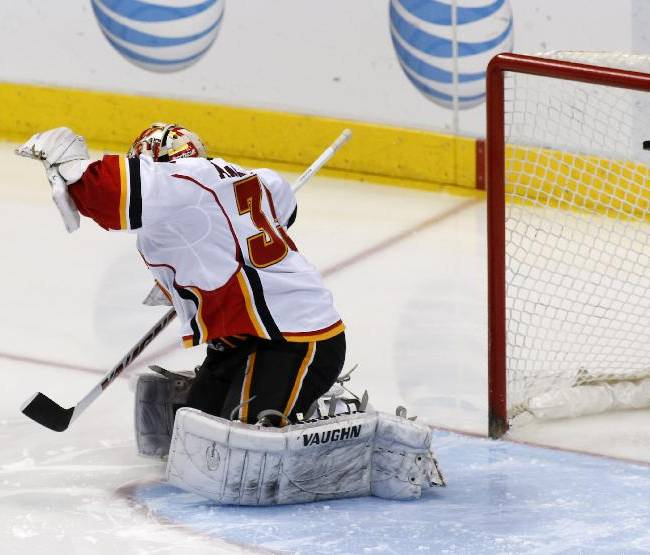 Calgary Flames goalie Joey MacDonald (35) gives up a goal in the second period of an NHL hockey game against the Dallas Stars Friday, March 14, 2014, in Dallas