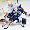 Vancouver Canucks' Zack Kassian (9) screens Edmonton Oilers goalie Ben Scrivens (30) as Scrivens makes the save during the second period of an NHL hockey game Saturday, April 12, 2014, in Edmonton, Alberta. The Oilers won 5-2 The Associated Press