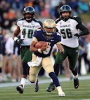 Navy's quarterback Keenan Reynolds, center, runs the ball as Hawaii's Jerrol Garcia-Williams, left, and Brenden Daley purue in the first half of an NCAA college football game on Saturday, Nov. 9, 2013, in Annapolis, Md. (AP Photo/Gail Burton)