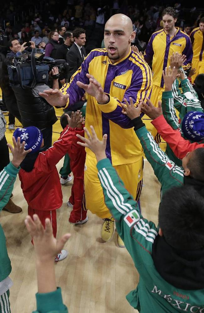Members of Triqui kids basketball team, made up of children from the mountainous  mountainous region of Oaxaca, Mexico, greet Los Angeles Lakers center Robert Sacre before an NBA basketball game between the Los Angeles Lakers and the Minnesota Timberwolves in Los Angeles, Friday, Dec. 20, 2013