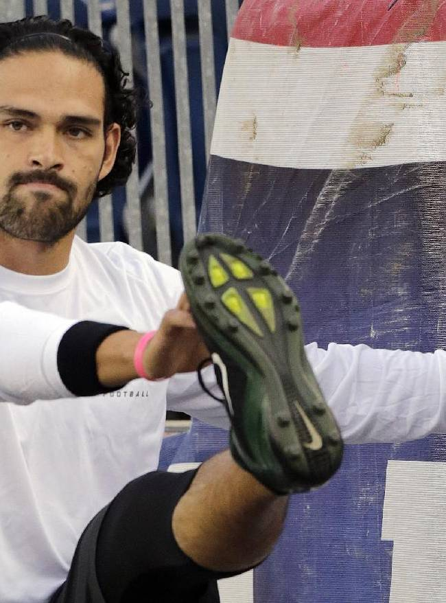 New York Jets injured quarterback Mark Sanchez stretches along a stadium wall before an NFL football between the Jets and the New England Patriots Thursday, Sept. 12, 2013, in Foxborough, Mass