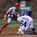 Cincinnati Reds shortstop Zack Cozart, left, catches the throw before tagging out Chicago Cubs' Emilio Bonifacio (64) who was attempting to steal second base during the third inning of a baseball game in Chicago, Sunday, April 20, 2014. Cincinnati won 8-2