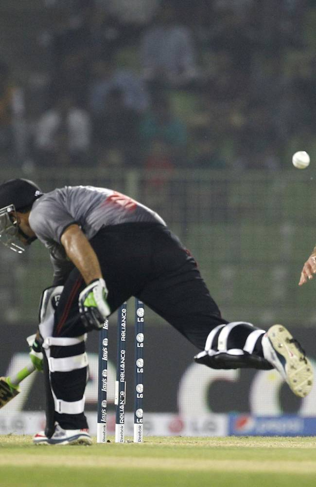 United Arab Emirates's Faizan Asif, center, runs to make his ground, as Ireland's Max Sorensen. right, waits to collect the ball during their ICC Twenty20 Cricket World Cup match in Sylhet, Bangladesh, Wednesday, March 19, 2014
