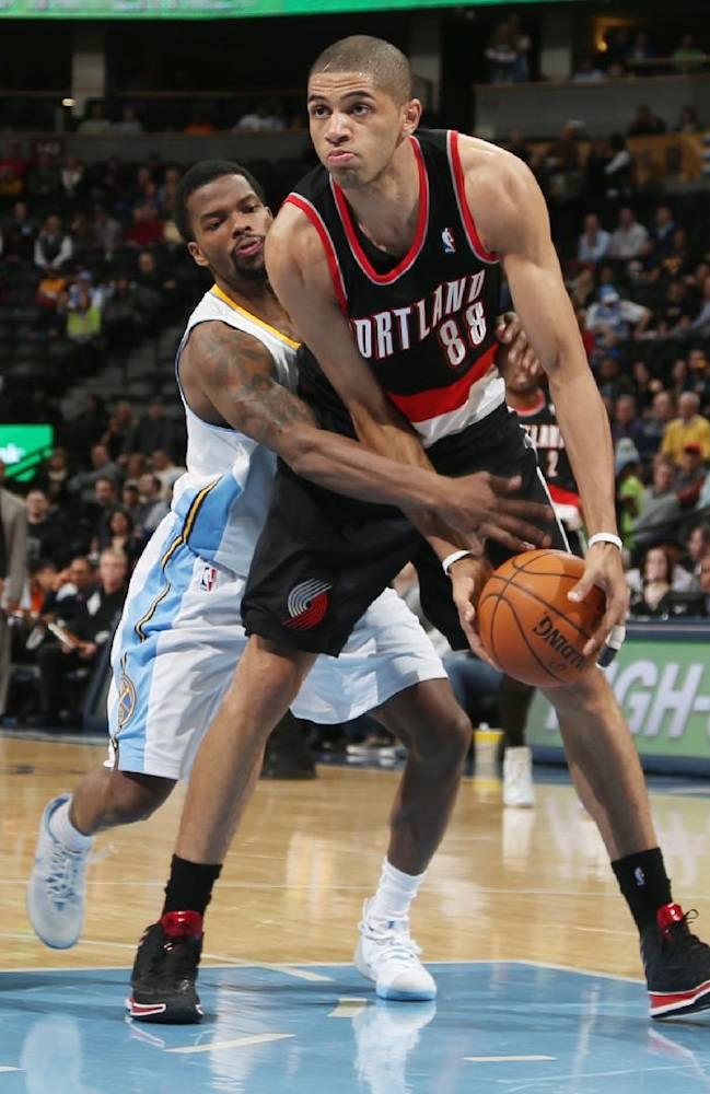 Portland Trail Blazers forward Nicolas Batum, front, of France, is fouled after picking up a loose ball by Denver Nuggets guard Aaron Brooks in the fourth quarter of an NBA basketball game in Denver, Tuesday, Feb. 25, 2014. Portland won 100-95
