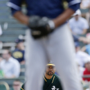 Oakland Athletics' Coco Crisp, behind, watches Milwaukee Brewers pitcher Wily Peralta as he leads off from first base during the third inning of a spring training baseball game Thursday, Feb. 27, 2014, in Scottsdale, Ariz The Associated Press
