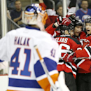 New Jersey Devils center Travis Zajac, second from right, is congratulated by left wing Patrik Elias, third from right, of the Czech Republic, and defenseman Adam Larsson, right, of Sweden, after scoring a goal against New York Islanders goalie Jaroslav