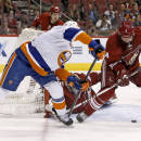 New York Islanders' John Tavares, left, gets off a shot between the legs of Phoenix Coyotes' Zbynek Michalek (4), of the Czech Republic, during the first period of an NHL hockey game Thursday, Dec. 12, 2013, in Glendale, Ariz. (AP Photo/Ross D. Franklin)