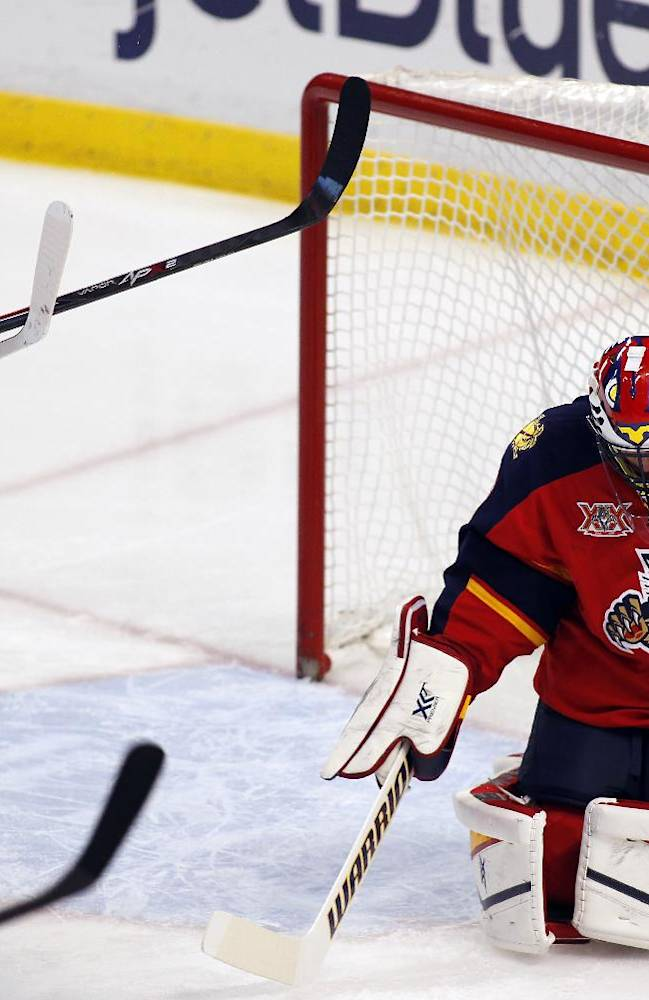 Florida Panthers goalie Scott Clemmensen (30) deflects a shot as Montreal Canadiens left wing Rene Bourque (17) skates by during the first  period of an NHL hockey game in Sunrise, Fla., on Sunday Dec. 29, 2013