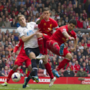 Liverpool's Luis Suarez, right, and Daniel Agger, center, and Tottenham's Michael Dawson, center left, lunge for the ball as Jordan Henderson, out of frame, scores from a free kick during their English Premier League soccer match at Anfield Stadium, Liver
