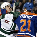 Minnesota Wild's Zach Parise (11) and Edmonton Oilers' Andrew Ference (21) mix it up during first period NHL hockey action in Edmonton, Alberta, on Tuesday Jan. 27, 2015 The Associated Press