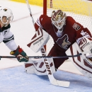 Arizona Coyotes' Devan Dubnyk, right, makes a glove save on a shot by Minnesota Wild's Mikko Koivu (9), of Finland, during overtime of an NHL hockey game Saturday, Dec. 13, 2014, in Glendale, Ariz. The Wild defeated the Coyotes 4-3 in a shootout The Asso