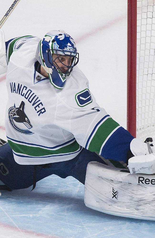 Vancouver Canucks goaltender Roberto Luongo makes a save against the Montreal Canadiens during the second period of an NHL hockey game Thursday, Feb. 6, 2014, in Montreal