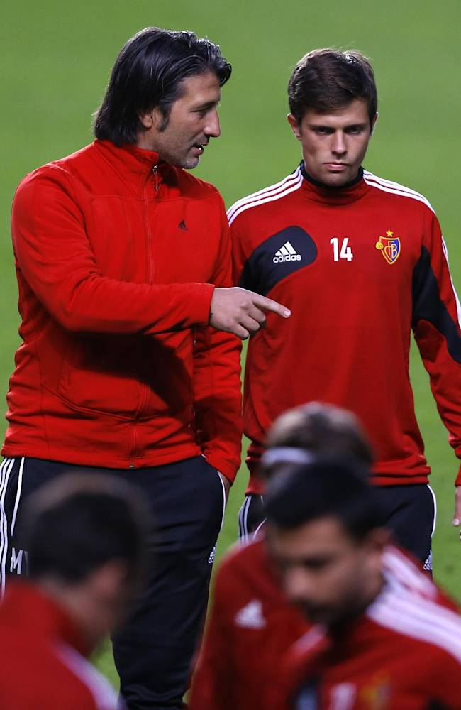 Basel coach Murat Yakin, left, talk to his player Basel's Valentin Stocker during a training session at Stamford Bridge Stadium in London, Tuesday, Sept. 17, 2013. Chelsea will play FC Basel in a Champions League match at Stamford Bridge on Wednesday