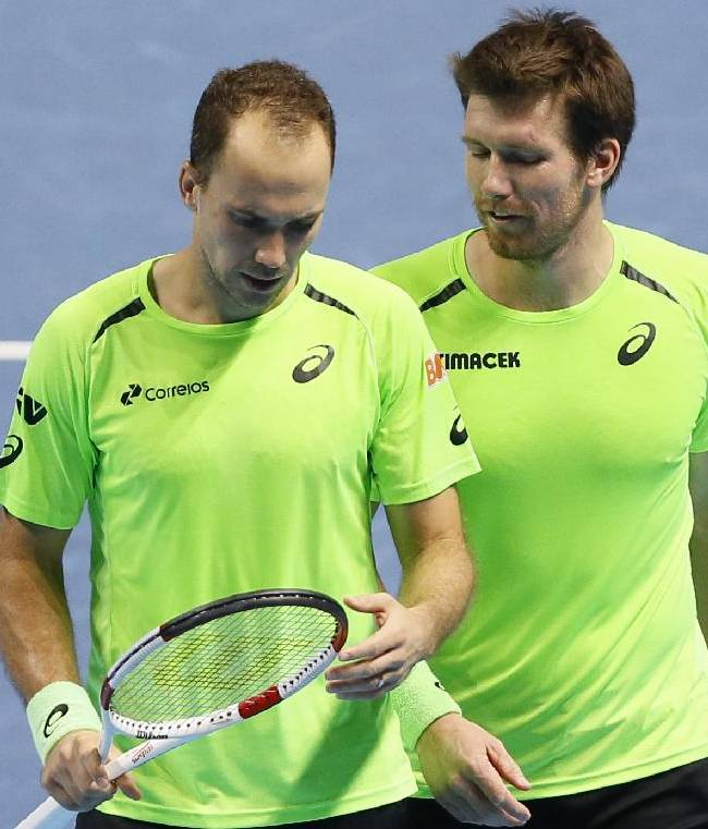 Brazil's Bruno Soares, left and Austria's Alexander Peya, Bob Bryan, talk, during their doubles ATP World Tour Finals tennis match, against Mike and Bob Bryan of the US, at the O2 Arena in London, Friday, Nov. 14, 2014