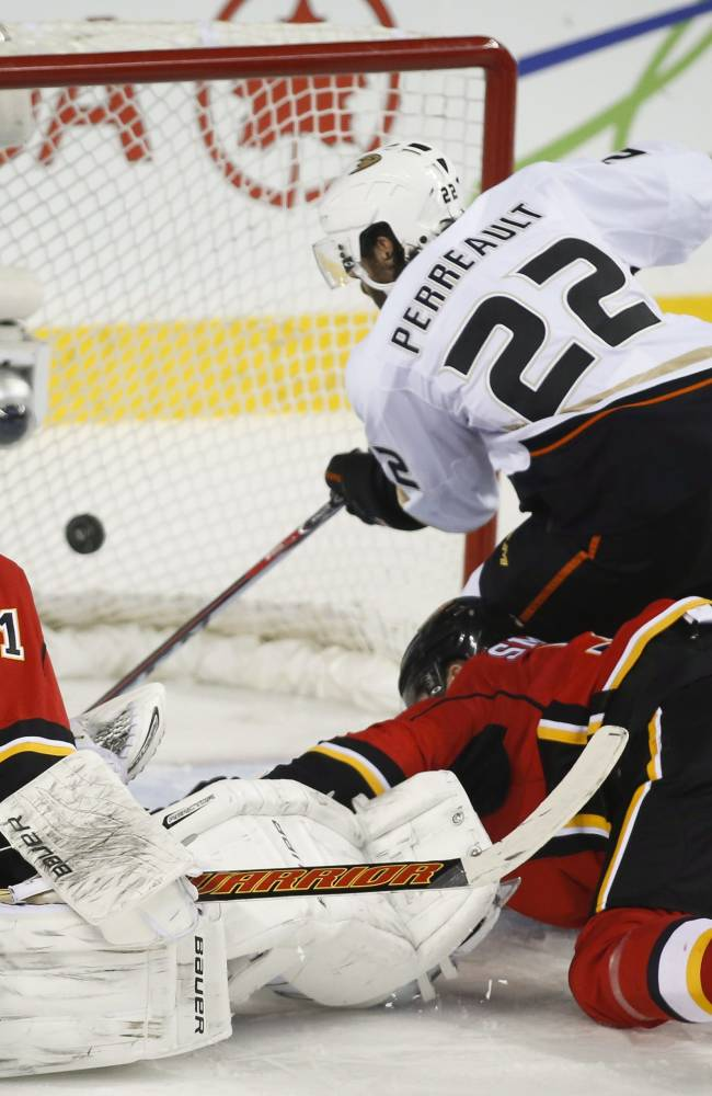 Anaheim Ducks' Mathieu Perreault, right, scores as Calgary Flames goalie Karri Ramo, left, from Finland, and Ladislav Smid, from the Czech Republic, look on during third period NHL hockey action in Calgary, Alberta, Wednesday, March 26, 2014. The Anaheim Ducks beat the Calgary Flames 3-2