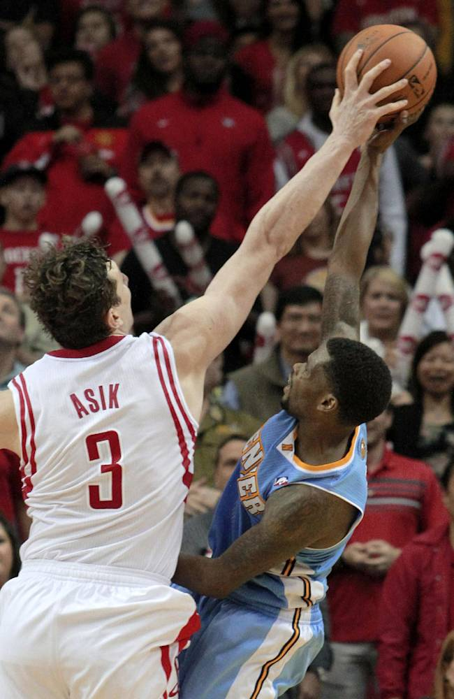 Houston Rockets center Omer Asik (3) blocks the shot of Denver Nuggets guard Aaron Brooks during overtime of an NBA basketball game in Houston on Sunday, April 6, 2014. The Rockets won 130-125