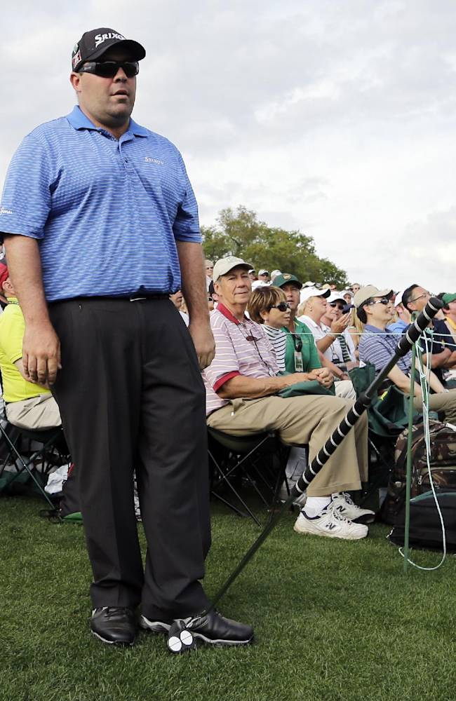 Kevin Stadler drops his putter after hitting out from the gallery on the 18th hole during the fourth round of the Masters golf tournament Sunday, April 13, 2014, in Augusta, Ga