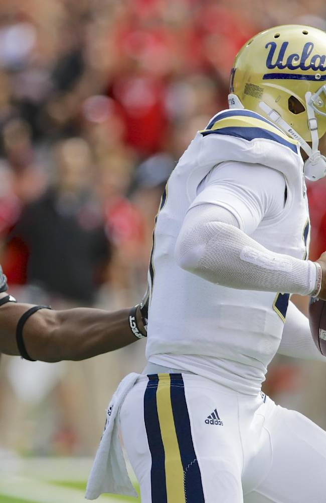 UCLA quarterback Brett Hundley (17) slips past Nebraska defensive end Randy Gregory (44) in the first half of an NCAA college football game in Lincoln, Neb., Saturday, Sept. 14, 2013