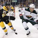 Boston Bruins center Patrice Bergeron (37) and Minnesota Wild center Mikael Granlund (64), of Finland, battle for the puck in the first period of an NHL hockey game in Boston, Tuesday, Oct. 28, 2014 The Associated Press