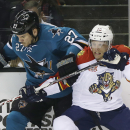 Florida Panthers' Joey Crabb (10) crashes against the boards with San Jose Sharks' Scott Hannan (27) during the first period of an NHL hockey game on Tuesday, March 18, 2014, in San Jose, Calif The Associated Press