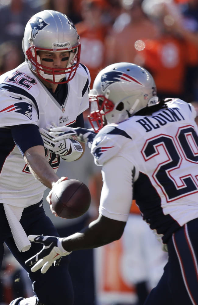 New England Patriots quarterback Tom Brady (12) hands of to New England Patriots running back LeGarrette Blount (29) during the first half of the AFC Championship NFL playoff football game against the Denver Broncos in Denver, Sunday, Jan. 19, 2014